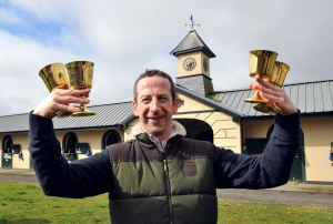 Jim Cullotty, trainer of Cheltenham Gold Cup winner Lord Windermere with his four Gold Cup trophies, three won with Best Mate. Pic: Healy Racing / Racingfotos.com (Courtesy of Great British Racing).
