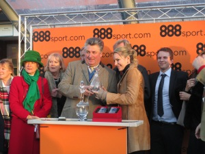 Paul Nicholls receives the trophy after winning the Tingle Creek Chase.