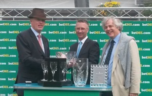 John Gosden accepts the trophy after Western Hymn's win at Sandown in April.