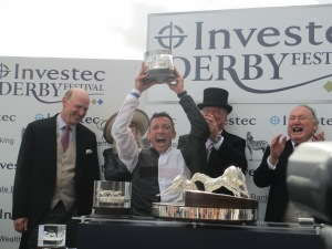 Frankie Dettori celebrates after winning the Investec Derby on Golden Horn as trainer John Gosden (left) looks on.